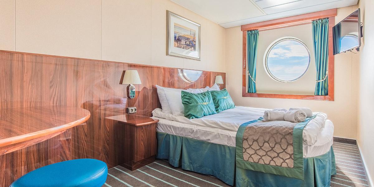 Vores store Deluxe-kahytter med plads til 1-3 personer har dobbeltseng og sovesofa, TV, badeværelse med brusebad og toilet.